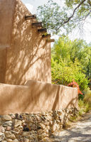 Tree casts shadows on adobe wall on Canyon Road in Santa Fe, New Mexico.