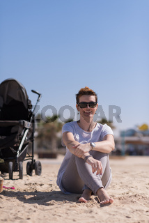 Young mother with sunglasses relaxing on beach