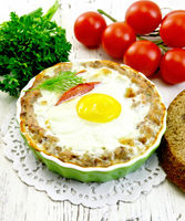 Tartlet meat with egg in pan on light board