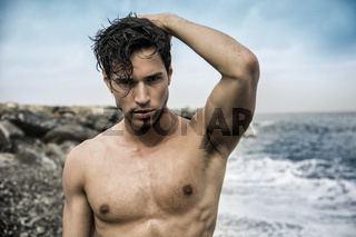 Young shirtless athletic man standing in water by ocean shore