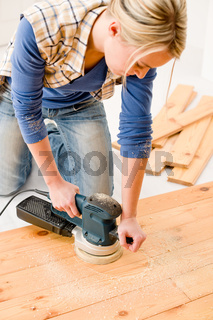 Home improvement - handywoman sanding wooden floor
