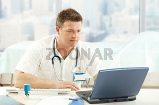 Mid-adult physician working with laptop