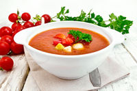 Soup tomato in white bowl with vegetables on towel