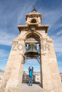 Tourist photographs bell on top of cathedral tower