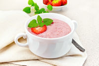 Soup strawberry in white bowl on granite table