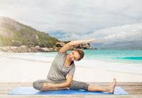happy woman doing yoga and stretching on beach