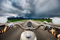 Biker on a motorcycle hurtling down the road in a lightning storm - Forggensee and Schwangau, Germany Bavaria