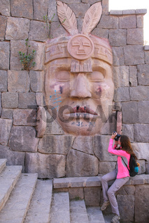 Woman photographing carving of Inca warrior on a wall in Chivay town, Peru