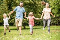 Glückliche Familie läuft im Garten