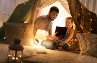 family with tablet pc in kids tent at home