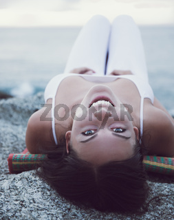 Girl in white is lying on the beach and smiling, sunset