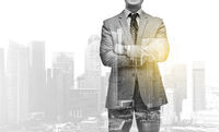 businessman with crossed arms over city buildings