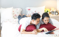 Couples lying using tablet on bed
