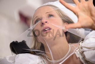 Junge blonde Frau im Brautkleid mit Schleier ängstlich auf der Flucht