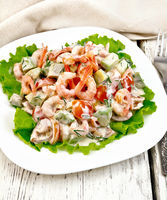 Salad with shrimp and tomato in white plate on light board