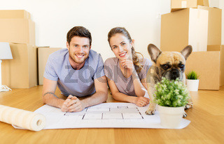 couple with boxes, blueprint and dog at new home