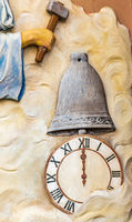 hand holding hammer on clock and bell