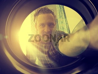 Happy man loading washing machine