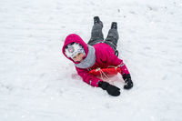 Girl in winter clothes on sled