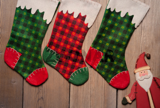 Christmas stockings hanging against wooden wall