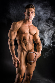 Naked male bodybuilder hiding crotch with american football ball