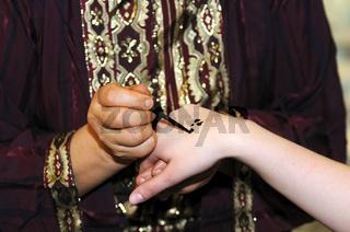 Arabische Frau malt ein Hennatattoo