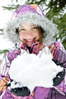Happy winter girl holding snow