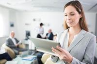 Junge Start-Up Frau schaut auf ihren Tablet PC