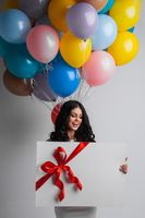 Woman with balloons and gift