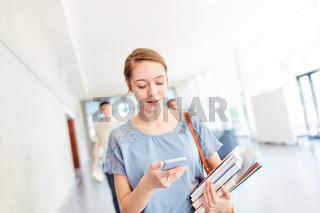 Studentin liest SMS auf dem Smartphone