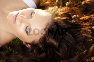 Close up of curly hair and face of beautiful girl lying on a lawn