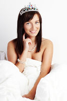Young beautiful woman wearing toy crown sitting on white bed