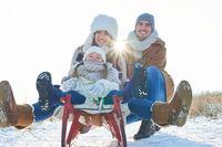 Glückliche Familie beim rodeln im Winter