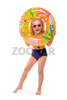 Pretty little girl in red striped bikini, blue bottoms, sunglasses and pink wreath stand stand with rubber ring in hand