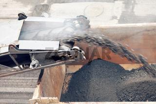 Road works. Asphalt removing machine loading powdered asphalt on the truck