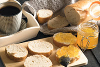Sliced french bread with peach jam and coffee
