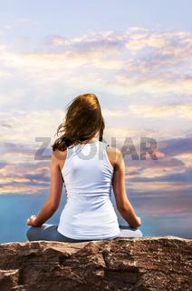Young girl meditating at sunset
