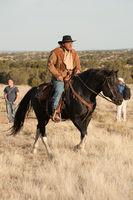 Cowboy rides a black horse.