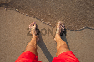 Man's legs on the sand beach and sea waves at sunset