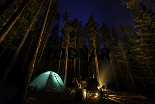 Two people camping in the forest with a fire
