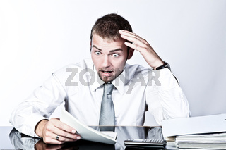 Young Corporate  Man Having A Shock When Reviewing Some Documents