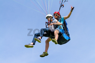 Instructor and paraglider flying in sky