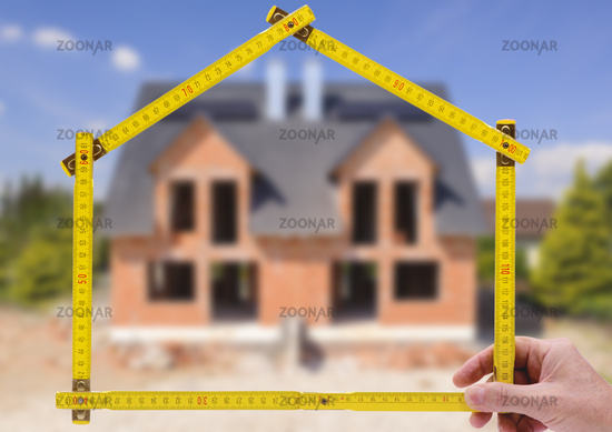 shell of house under construction with folding ruler in hand of real estate agent