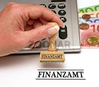 Finanzamt - Stempel mit Hand und Geld