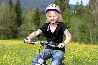 Mädchen fährt Fahrrad im Frühling
