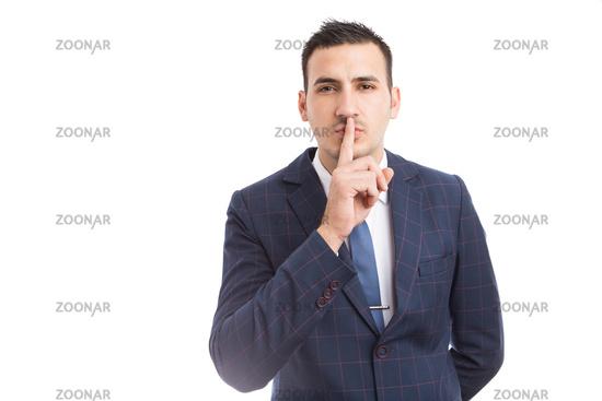 Sales man or broker touching lips as shush gesture