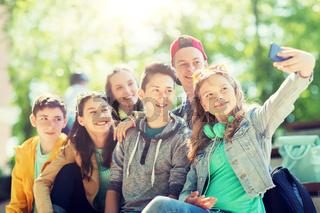 happy teenage students taking selfie by smartphone