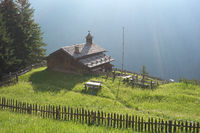 An Alpine meadow with old wooden farmhouse, Dolomites