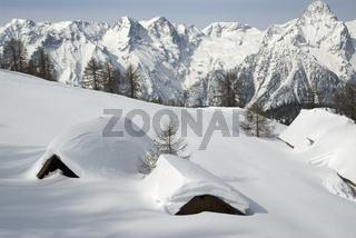 Tief verschneite Almhütte in Hinterstoder im Hintergrund das Tote Gebirge, Oberösterreich, Österreich