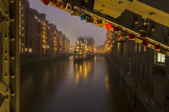 Poggenmühlen bridge perspective at water castle at night, historic Speicherstadt warehouse district,
